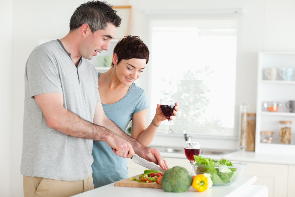 Man cutting vegetables while is woman is watching in a kitchen